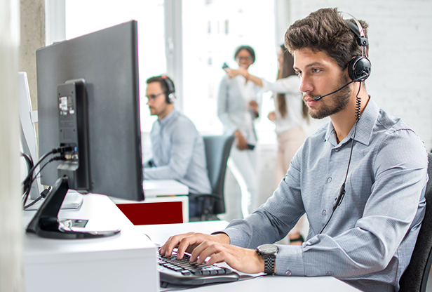 Young handsome male customer support phone operator with headset working in call center.